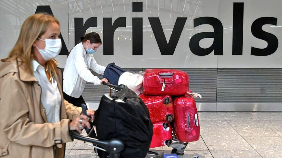 In June 2021, passengers wheel their luggage carts through Terminal 5 at Heathrow Airport in London.